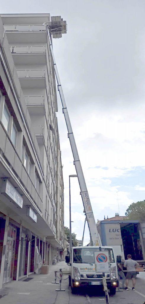 Foto di un'autoscala al lavoro. Noleggio scala per arredamenti contract in condominio - Noleggi.me